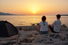 Back view of family, sitting on rock beach, admiring setting sun over sea. Back view of happy young family, sitting on rock beach near tent and admiring setting stock photography