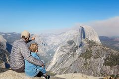 Family in yosemite. Back view of family of two, father and son, sitting together at glacier point and enjoying view of half dome and yosemite valley in yosemite Stock Images