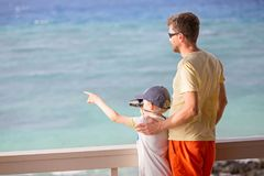 Family on vacation. Back view of family of two, father and son, using binoculars and looking ahead and pointing at something with finger, vacation concept Stock Photography