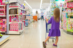 Back view of fashion girl with trolley in kid Stock Images