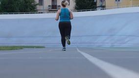 Plus size sporty female jogging on city stadium