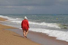 Back view of a fat woman walking alone on a sunny day on the beach of the Mediterranean Sea Royalty Free Stock Image