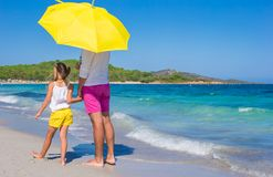 Back view of father and daughter at white beach Royalty Free Stock Image