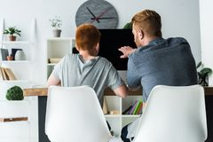 back view of father helping son doing homework at home and pointing stock photos