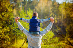Back view of father  his son on shoulders on nature Stock Photos