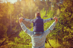Back view of father  his son on shoulders on nature. Royalty Free Stock Photography