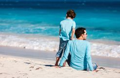Father and son at beach. Back view of father and son on beach vacation royalty free stock photography