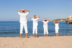 Back view of father and sons walking on beach Stock Images