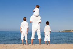 Back view of father and sons walking on beach. Outdoor Royalty Free Stock Photography