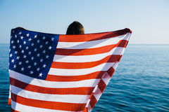 Back view of female with American flag against  sea Royalty Free Stock Image