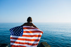 Back view of female with American flag against  sea Royalty Free Stock Photos