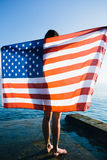 Back view of female with American flag against  sea Royalty Free Stock Images