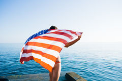 Back view of female with American flag against  sea Stock Photos