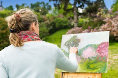 Back view of a female artist working outdoors in the park or gar. Den on a trestle and easel painting with oils and acrylics during an art class Stock Photography
