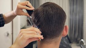 Female barber haircut doing male hair style. Back view of female barber haircut doing male hair style royalty free stock photography