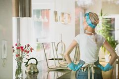Back view of female cleaner. View from back at female cleaner wearing household cleaning clothes standing in her tidy kitchen after sweeping the floor Stock Photography