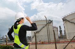 Back view of Female construction worker against gas separation plant.  royalty free stock image