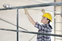 Back view of female contractor placing iron rod on scaffold Stock Photography