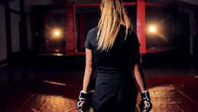 A female fighter shakes her arms walking closer to a cage. stock video