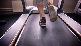 Back view of female legs walking and running on treadmill in gym, woman training stock video