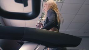 Back view of female legs walking and running on treadmill in gym, woman training. 4k stock footage