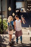 Back view of female and male teenagers with skateboard have active activities outdoor during summer recreation, ride. Skateboard through street, dressed in Stock Photography
