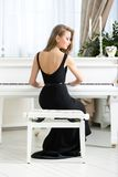 Back view of female musician sitting and playing piano Royalty Free Stock Photo