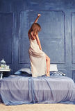 Back view of a female in a nightgown dancing on the bed. Low angle of a female in a nightgown dancing on the bed. Back view of a slim lady in a pastel nightdress Stock Photos