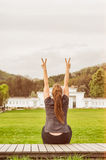 Back view of female showing double peace or victory gesture. Back view of happy female showing double peace or victory gesture and relaxing outside in the park Stock Photography