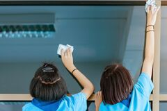 Back view of female students are helping to wipe the glass with wet newspaper at school.