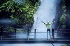 Female tourist enjoys Situ Gunung waterfall view stock photo