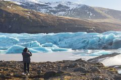 Back view of female tourists photographer taking picture of beautiful evening scenery of Skaftafell glacier Vatnajokull national stock image
