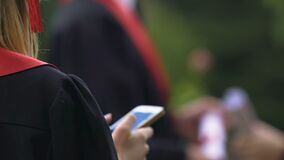 Back view of female university graduate typing and sending message on smartphone. Stock footage stock video footage
