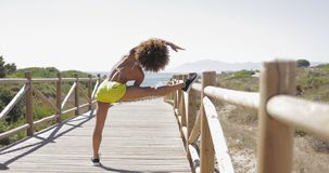 Fit woman training on pier. Back view of fit ethnic woman in bikini and sportive short warming up legs before workout on wooden pier with view of sea on Stock Images