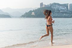 Back view of fit slim girl running barefoot on seashore wearing bikini. Young woman doing cardio exercise beach lit in royalty free stock images