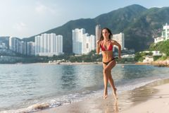 Back view of fit slim girl running barefoot on seashore wearing bikini. Young woman doing cardio exercise beach lit in stock image