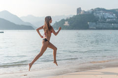 Back view of fit slim girl running barefoot on seashore wearing bikini. Young woman doing cardio exercise beach lit in Stock Photography