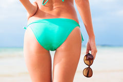 Back view of fit young woman in green bikini with. Sunglasses in hand. This image has attached release royalty free stock image