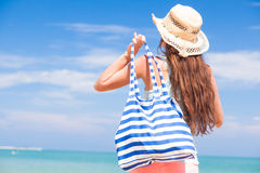 Back view of a fit young woman with stripy bag at Stock Images