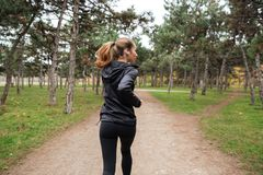 Back view of a fitness woman jogging. Outdoors Royalty Free Stock Photography