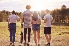 Back view of four friends have stroll across meadow, hold acoustic guitar, have pleasant talk, recreat during summer time, enjoy s. Unshine, pose outdoor royalty free stock photography