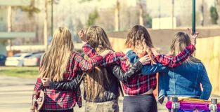 Back view of four girl friends hugging. At the skate park. Friendly hugs of best friends. Friendship and unity concept Royalty Free Stock Photos