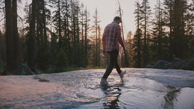 Back view of free young man stepping into small water stream enjoying amazing sunset hike at Yosemite park slow motion. Excited Caucasian male tourist in stock video
