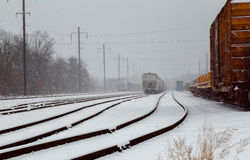 back view of Freight train running on the railway tracks in winter while is snowing Royalty Free Stock Images