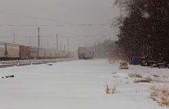 back view of Freight train running on the railway tracks in winter while is snowing Royalty Free Stock Photo