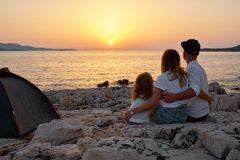 Back view of friendly family admiring setting sun over sea. Back view of cute young family, sitting on rock beach near tent and admiring setting sun over sea royalty free stock photos