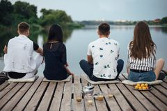 Back view of friends relaxing on river pier royalty free stock images