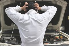Back view of frustrated stressed young mechanic man in white uniform touching his head with hands against car in open hood at the Royalty Free Stock Photo