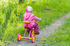 Back view full length portrait of little girl riding kids pink and yellow tricycle on park track Stock Photos