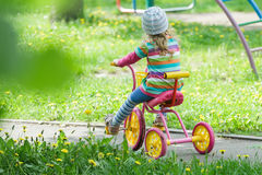 Back view full length portrait of preschooler girl riding kids pink and yellow tricycle on playground track Royalty Free Stock Images